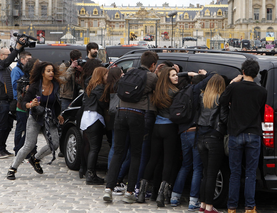 Photo - Fans gather to watch guests arriving, as they look inside one of the cars for Kim Kardashian, Kanye West and their guests, at the entrance of the Chateau de Versailles in Versailles, France, west of Paris, Friday, May 23, 2014. The gates of the Chateau de Versailles, once the digs of Louis XIV, will be thrown open to Kim Kardashian, Kanye West and their guests for a private evening on the eve of their marriage. (AP Photo/Michel Spingler)
