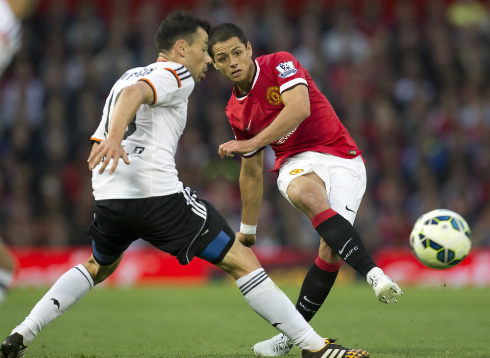 Photo - FILE - This is a Tuesday Aug. 12, 2014   file photo of Manchester United's Javier Hernandez  as he fires a shot past Valencia's Javi Fuego during a pre season friendly soccer match at Old Trafford Stadium, Manchester, England.  Real Madrid has signed Mexico striker Javier Hernandez on a season-long loan from Manchester United. Madrid announced the deal hours before the close of the summer transfer window on Monday Sept. 1, 2014. (AP Photo/Jon Super, File)