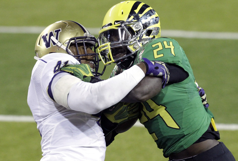 Oregon running back Kenjon Barner, right, battles for yardage against Washington defender Travis Feeney during the second half of their NCAA college football game against Washington in Eugene, Ore., Saturday, Oct. 6, 2012. Barner, who went into the game ranked 10th in the nation with an average of 121 yards rushing per game, ran for 122 yards as they beat Washington 52-21.(AP Photo/Don Ryan)