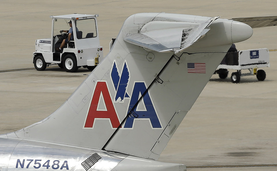 Photo - In this May 15, 2014 photo, a ramp worker rolls past an American Airlines McDonnell Douglas MD-82  at the Tampa International Airport in Tampa , Fla. American Airlines reports quarterly financial results on Thursday, July 24, 2014. (AP Photo/Chris O'Meara)