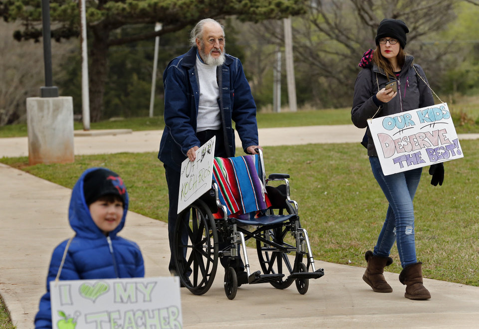 Photo - Former Union President Ted Metscher uses a wheel chair as a walker as he begins a walk from Northeast Academy to the Oklahoma teachers rally at the State Capitol on Monday, April 2, 2018 in Oklahoma City, Okla.  Photo by Steve Sisney, The Oklahoman
