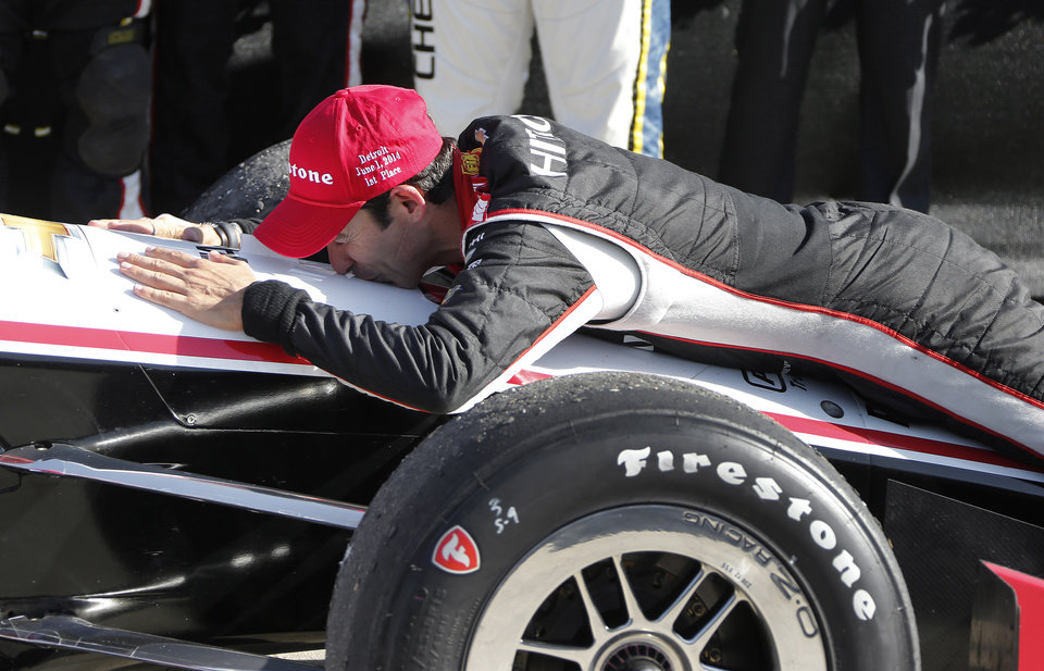 Photo - Helio Castroneves kisses his car in the winners circle after his victory in the second race of the IndyCar Detroit Grand Prix auto racing doubleheader in Detroit Sunday, June 1, 2014. (AP Photo/Bob Brodbeck)
