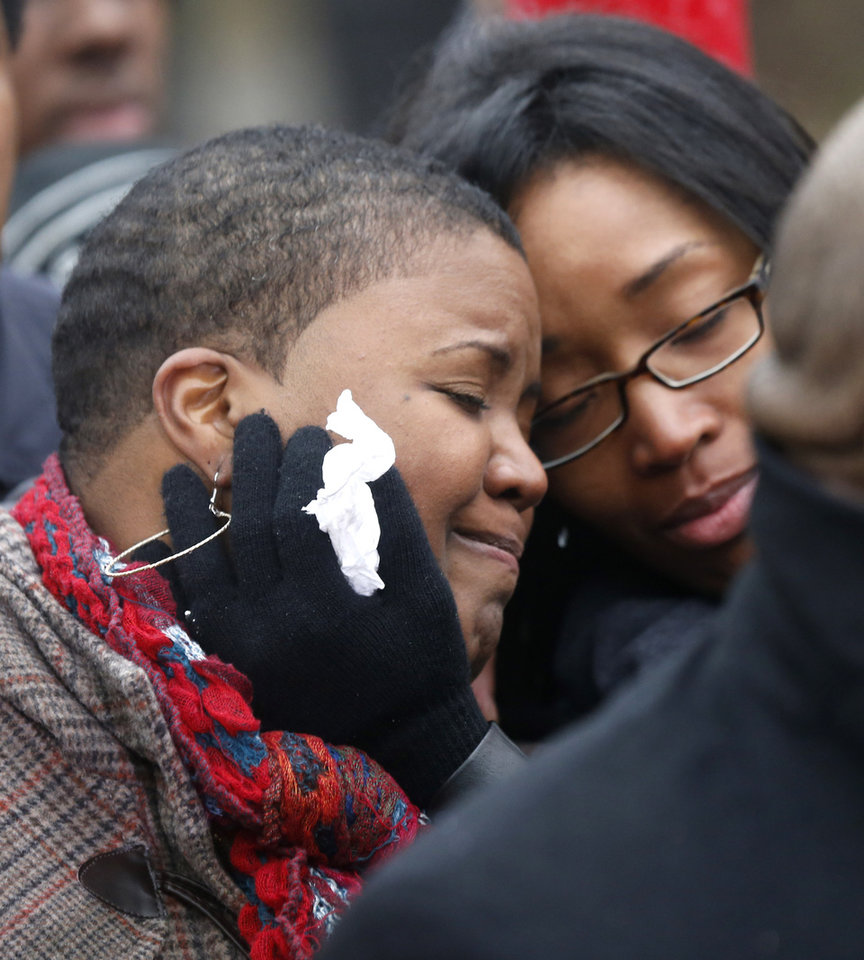 Photo - Cleopatra Pendelton, left, is consoled by her sister Kimiko Pettis, during a news conference with Chicago Police Superintendent Garry McCarthy seeking help from the public in solving the murder of Pendelton's daughter Hadiya Wednesday, Jan. 30, 2013, in Chicago.  Hadiya, 15, who had performed in President Barack Obama's inauguration festivities, was killed in a Chicago park as she talked with friends by a gunman who apparently was not even aiming at her. The city's 42nd slaying is part of Chicago's bloodiest January in more than a decade, following on the heels of 2012, which ended with more than 500 homicides for the first time since 2008. It also comes at a time when Obama, spurred by the Connecticut elementary school massacre in December, is actively pushing for tougher gun laws. (AP Photo/Charles Rex Arbogast)