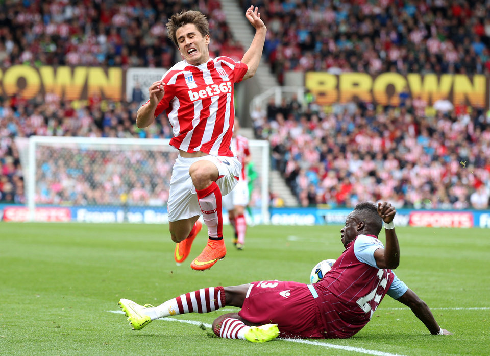 Photo - Aston Villa's Aly Cissokho, right, and Stoke City's Bojan battle for the ball during their English Premier League soccer match at The Britannia Stadium, Stoke, England, Saturday, Aug. 16, 2014. (AP Photo/Lynne Cameron, PA Wire)    UNITED KINGDOM OUT    -   NO SALES   -   NO ARCHIVES