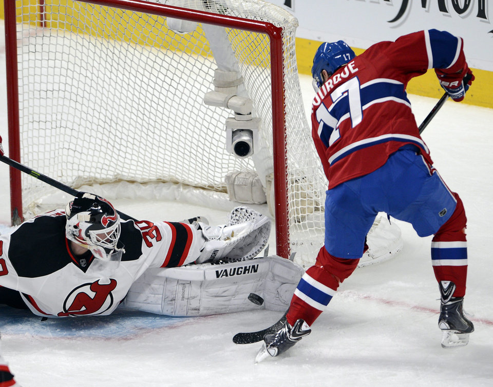 Photo - New Jersey Devils goalie Martin Brodeur (30) stops Montreal Canadiens left wing Rene Bourque (17) during second period National Hockey League action, Tuesday, Jan. 14, 2014, in Montreal. (AP Photo/The Canadian Press, Ryan Remiorz)