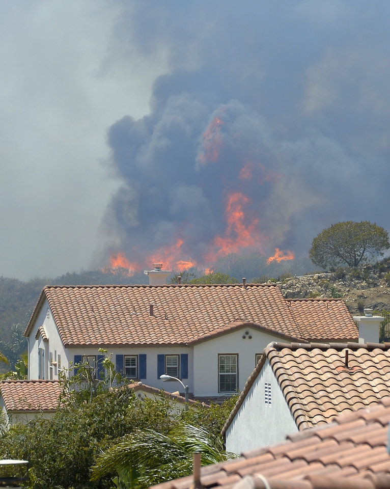 Photo - Fire burns behind homes during a wildfire that burned several thousand acres, Thursday, May 2, 2013, in Thousand Oaks, Calif.   (AP Photo/Mark J. Terrill)