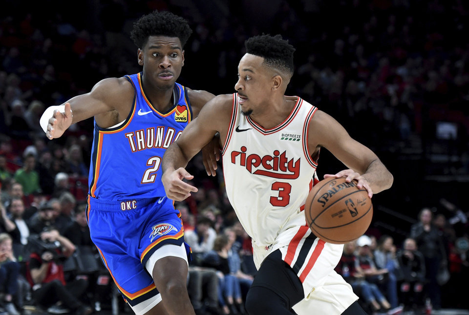 Photo - Portland Trail Blazers guard CJ McCollum, right, drives to the basket zx Oklahoma City Thunder guard Shai Gilgeous-Alexander defends during the second half of an NBA basketball game in Portland, Ore., Wednesday, Nov. 27, 2019. The Blazers won 136-119. (AP Photo/Steve Dykes)
