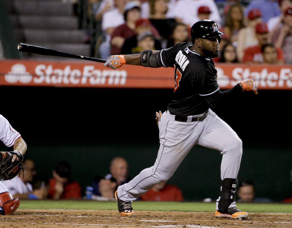 Photo - Miami Marlins' Marcell Ozuna scores Reed Johnson on a sacrifice fly during the third inning of a baseball game against the Los Angeles Angels in Anaheim, Calif., Monday, Aug. 25, 2014. (AP Photo/Chris Carlson)
