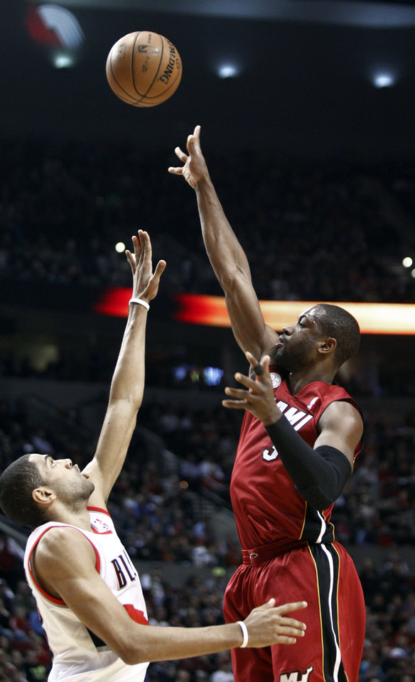 Photo - Miami Heat guard Dwayne Wade, right, shoots over Portland Trail Blazers forward Nicolas Batum, from France, during the first quarter of an NBA basketball game in Portland, Ore., Thursday, Jan. 10, 2013. (AP Photo/Don Ryan)