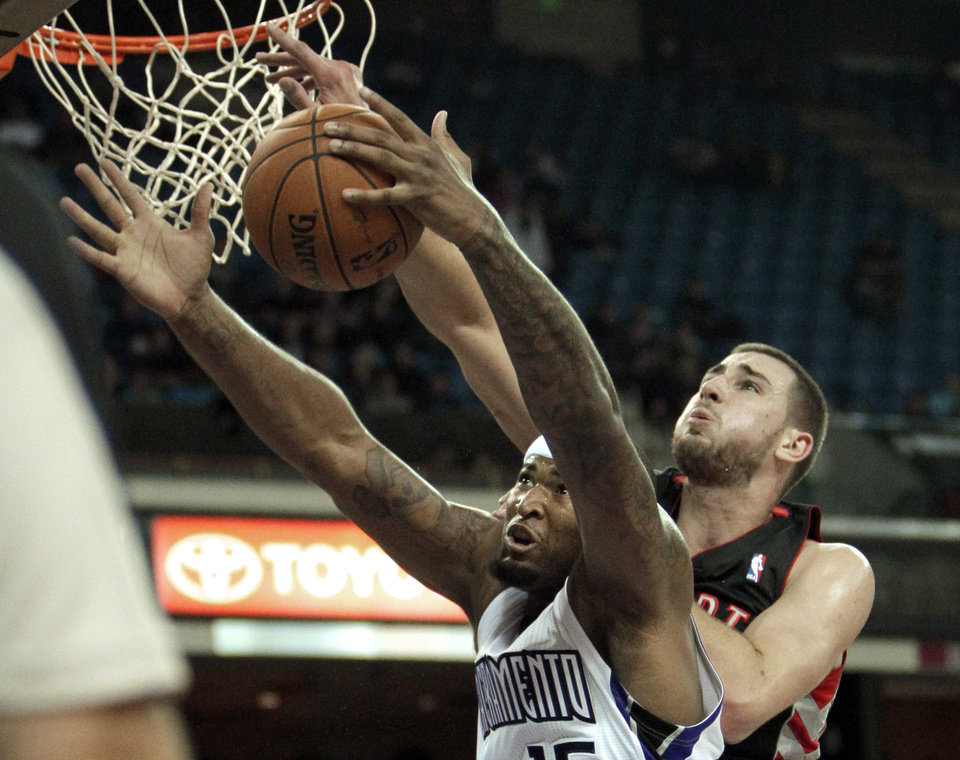 Sacramento Kings center DeMarcus Cousins, left, grabs a rebound in front of Toronto Raptors center Jonas Valanciunas, of Lithuania, during the first quarter of an NBA basketball game in Sacramento, Calif., Wednesday, Dec. 5, 2012. (AP Photo/Rich Pedroncelli)