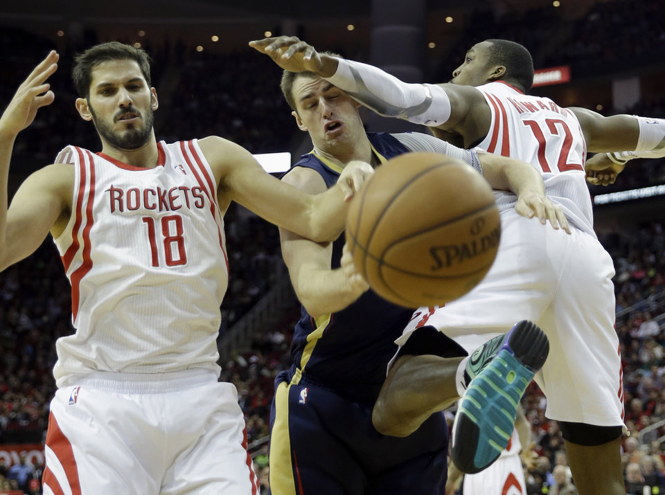 New Orleans Pelicans' Jason Smith, center, is fouled by Houston Rockets' Dwight Howard (12) as Omri Casspi (18) also defends during the fourth quarter of an NBA basketball game Saturday, Dec. 28, 2013, in Houston. The Rockets won 107-98. (AP Photo/David J. Phillip)
