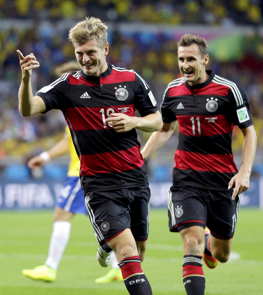 Photo - Germany's Toni Kroos, left, celebrates with Miroslav Klose (11) after scoring his side's fourth goal during the World Cup semifinal soccer match between Brazil and Germany at the Mineirao Stadium in Belo Horizonte, Brazil, Tuesday, July 8, 2014. (AP Photo/Natacha Pisarenko)
