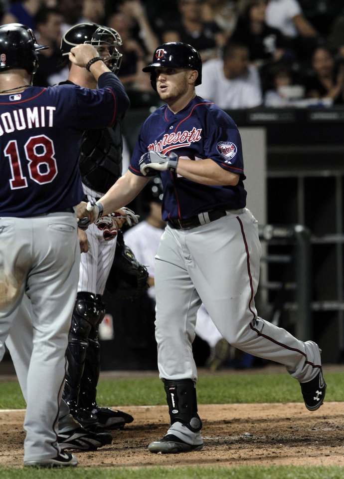 Photo -   Minnesota Twins' Chris Parmelee is greeted by Ryan Doumit after hitting a three-run home run against the Chicago White Sox during the fifth inning of a baseball game, Tuesday, Sept. 4, 2012, in Chicago. (AP Photo/John Smierciak)