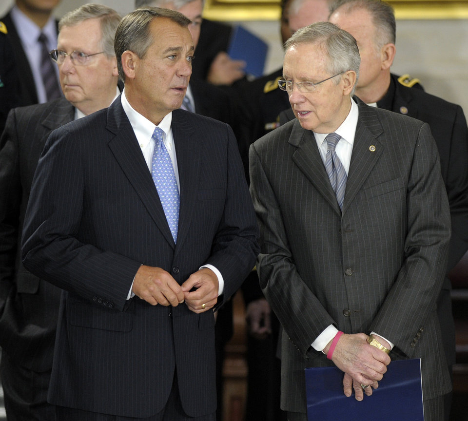 Photo - House Speaker John Boehner of Ohio, second from left, speaks with Senate Majority Leader Harry Reid of Nevada, right, before the lying in state of Sen. Daniel Inouye, D-Hawaii, the second-longest-serving senator in history, in the Capitol Rotunda in Washington, Thursday, Dec. 20, 2012. Inouye was a Medal of Honor recipient who represented his state in the U.S. House and then the Senate, where he served for five decades. He died Monday evening at age 88 of respiratory complications. (AP Photo/Susan Walsh)