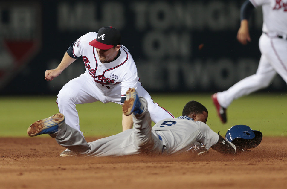 Photo - Los Angeles Dodgers' Dee Gordon (9) steals second base as Atlanta Braves second baseman Phil Gosselin (15) applies the late tag in the fifth inning of a baseball game Wednesday, Aug. 13, 2014, in Atlanta. (AP Photo/John Bazemore)