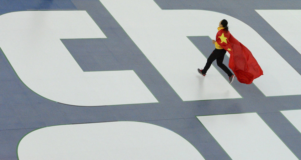 Photo - Gold medallist China's Zang Hong runs with her national flag for the flower ceremony after the women's 1,000-meter speedskating race at the Adler Arena Skating Center during the 2014 Winter Olympics in Sochi, Russia, Thursday, Feb. 13, 2014. (AP Photo/Antonin Thuillier, Pool)