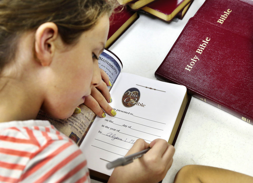 Photo - Alyssa Dalley, a student at St. John's Lutheran School, writes a personal note on the opening pages of a Bible that will be distributed to tornado victims as part of the CHRISTMAS Cares Moore outreach event at St. John's Lutheran Church in Moore.   Jim Beckel - THE OKLAHOMAN