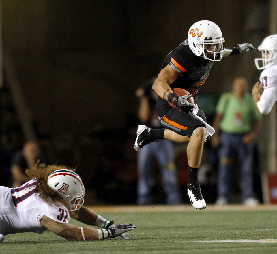Photo - Oklahoma State's Josh Cooper leaps past Arizona's Taimi Tutogi during the Cowboys 37-14 win on Thursday in Stillwater. PHOTO BY BRYAN TERRY, The Oklahoman