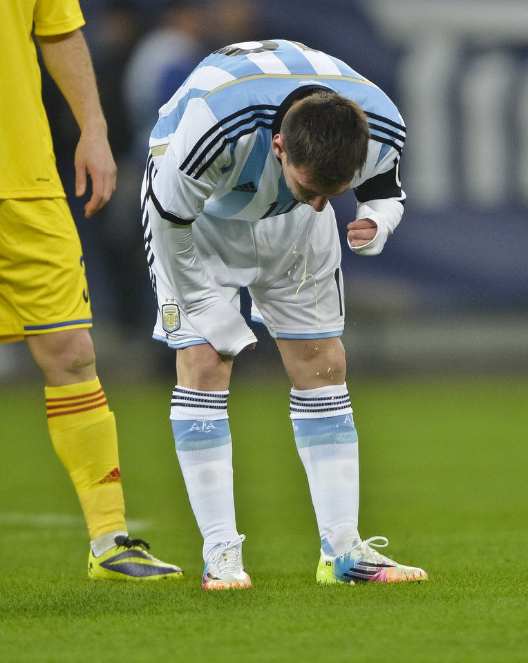 Photo - Argentina's Lionel Messi appears to vomit during an international friendly soccer game against Romania on the National Arena stadium in Bucharest, Romania, Wednesday, March 5, 2014. (AP Photo) ROMANIA OUT