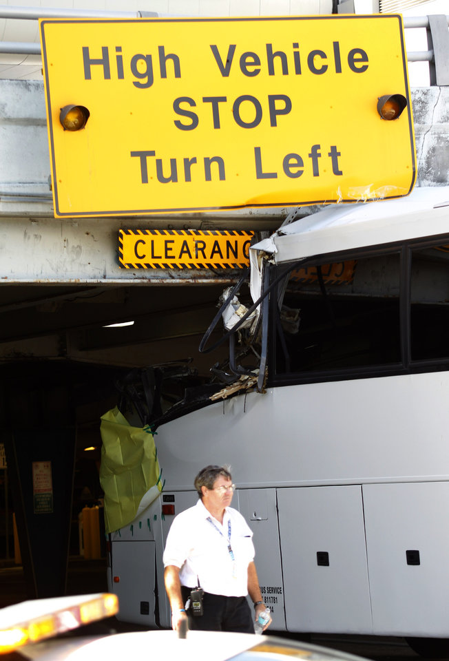 Photo - An airport worker walks past a bus which hit a concrete overpass at Miami International Airport in Miami on Saturday, Dec. 1, 2012. The vehicle was too tall for the 8-foot-6-inch entrance to the arrivals area, and buses are supposed to go through the departures area which has a higher ceiling, according to an airport spokesperson. (AP Photo/Wilfredo Lee)