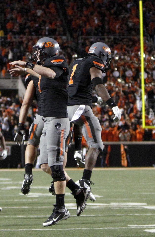 Photo - Oklahoma State's Brandon Weeden (3) and Joseph Randle (1) celebrate Randle's game winning touchdown during a college football game between the Oklahoma State University Cowboys (OSU) and the Kansas State University Wildcats (KSU) at Boone Pickens Stadium in Stillwater, Okla., Saturday, Nov. 5, 2011.  Photo by Sarah Phipps, The Oklahoman