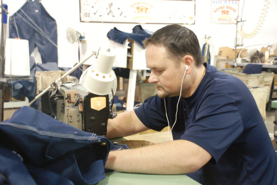 Round House employee Jeff Lawerance sews a pair of jeans. The company says it will add to its manufacturing facility and hire 40 workers. PHOTOS PROVIDED