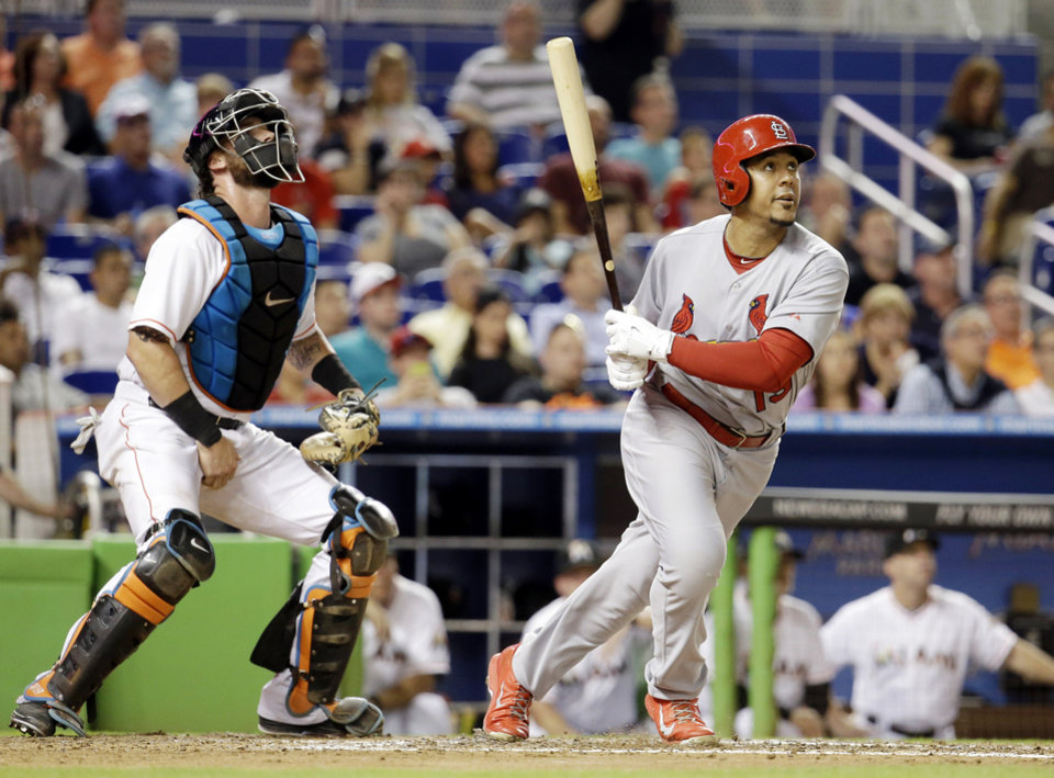 Photo - St. Louis Cardinals' Jon Jay watches after hitting a two-run home run as Miami Marlins catcher Jarrod Saltalamacchia, left, looks on in the fourth inning during a baseball game, Monday, Aug. 11, 2014, in Miami. (AP Photo/Lynne Sladky)