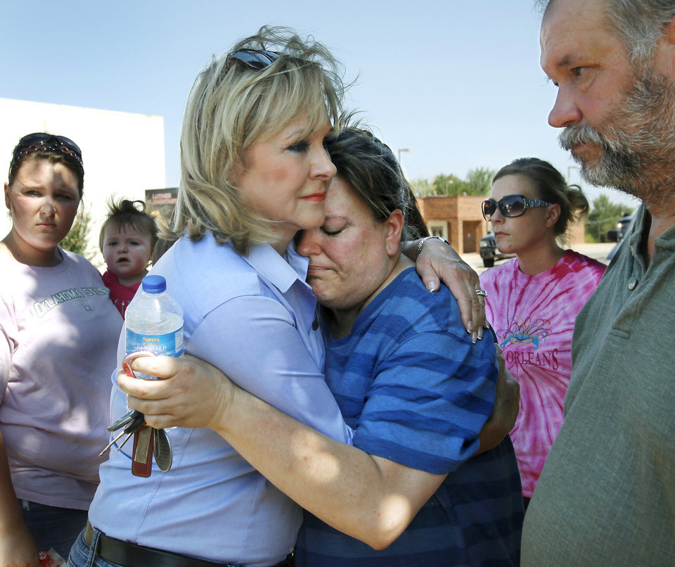 Photo - Gov. Mary Fallin, left,  offers a hug and supportive words to homeowners who lost their homes in the Luther wildfire. Fallin hugs Rebecca Kolar who was in tears as she spoke to the governor in front of her home at 908 S. Dogwood Street.  At right is her husband, Douglas Kolar. The Kolars and their two children lived in their house for 13 years before flames razed it. Residents  in Luther were allowed to return to the their homes early Saturday, Aug. 4, 2012, after they fled a rapidly moving wildfire yesterday that consumed at least seven structures on South Dogwood Street, leaving smoldering ashes where family homes once stood.  
