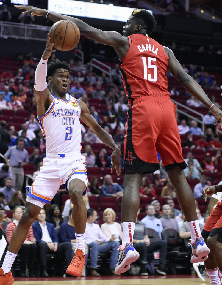 Photo - Oklahoma City Thunder guard Shai Gilgeous-Alexander (2) passes around Houston Rockets center Clint Capela during the first half of an NBA basketball game, Monday, Oct. 28, 2019, in Houston. (AP Photo/Eric Christian Smith)