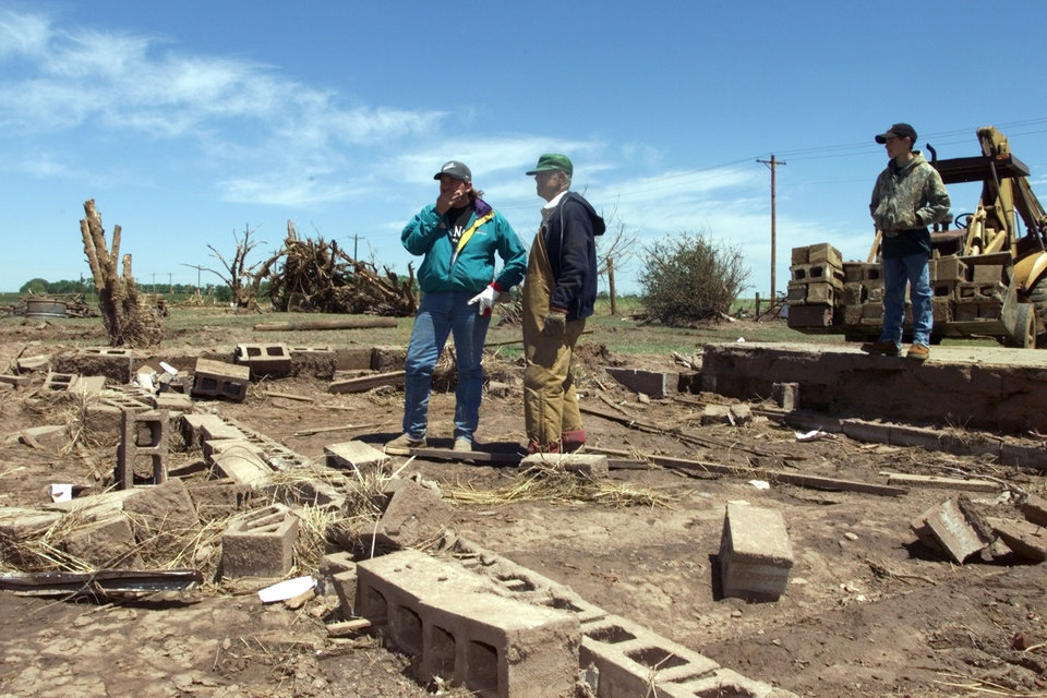 Tornado victims, damage: Kevin Harrison (left) and his father-in-law Laddie Fuksa examine all that remains of a two story frame house in Dover.  Kevin owned two houses next to each other that vanished as he and his family took shelter in a storm cellar.  The shelter caved in on the family which included son Colton, thirteen, right.