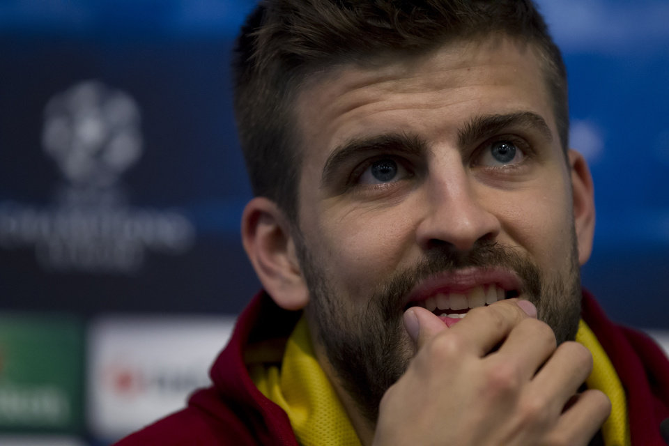 Photo - Barcelona's Gerard Pique smiles as he answers questions during a press conference at Manchester City's Etihad Stadium, Manchester, England, Monday Feb. 17, 2014. Barcelona will play Manchester City on Tuesday in a Champions League first knock out round soccer match. (AP Photo/Jon Super)