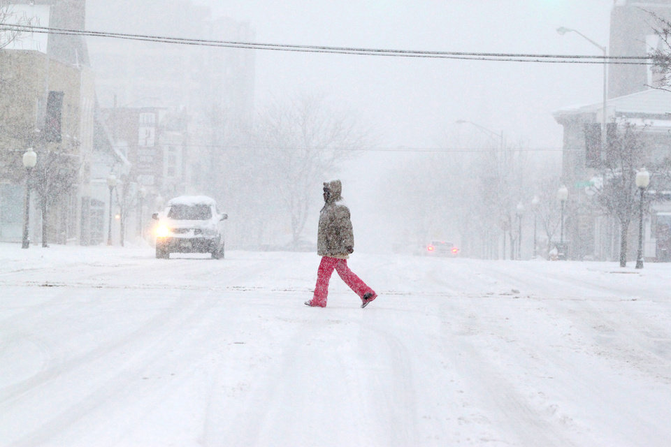 Photo - A pedestrian crosses Franklin Street as heavy snow falls Tuesday, March 5, 2013 in Michigan City, Ind. (AP Photo/The News Dispatch, Bob Wellinski)