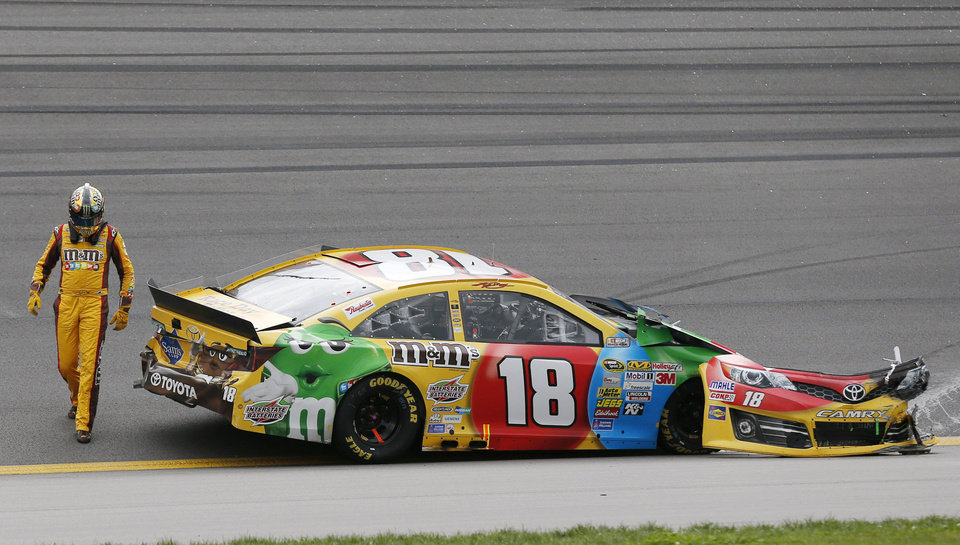 Photo - Driver Kyle Busch (18) walks around his wrecked race car during a NASCAR Sprint Cup series auto race at Kansas Speedway in Kansas City, Kan., Sunday, Oct. 6, 2013. (AP Photo/Orlin Wagner)