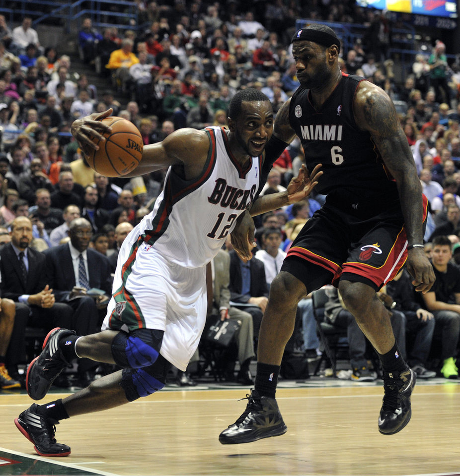 Milwaukee Bucks' Luc Richard Mbah a Moute (12) drives to the basket around Miami Heat's LeBron James (6) during the second half of an NBA basketball game on Saturday, Dec. 29, 2012, in Milwaukee. (AP Photo/Jim Prisching)