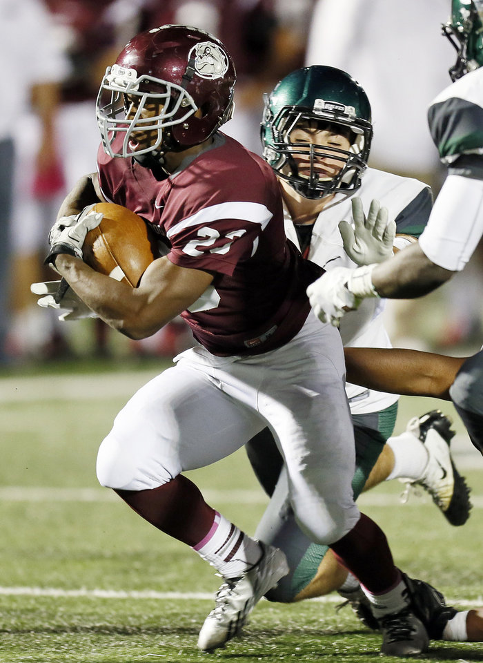 Photo - Edmond Memorial's Warren Wand carries the ball past Edmond Santa Fe's Garrett Russell during Friday night's matchup at Wantland Stadium. Photo by Nate Billings, The Oklahoman