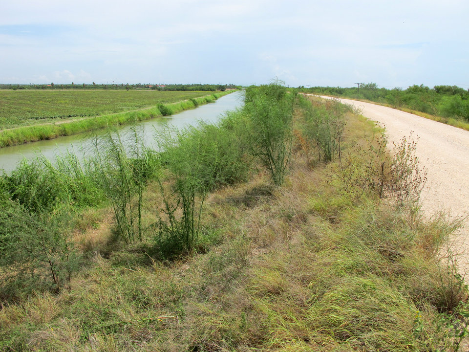 Photo - In this Aug. 9, 2014 photo, the main canal supplying water to the city of Mission, Texas is shown. At this spot on the night of Aug. 6, 2014, Border Patrol agents arresting immigrants mistook seven armed militia members for state troopers. The presence of armed militia members working on their own in a region known for human smuggling, drug smuggling and illegal immigration has added one more variable to an already complex and tense situation. (AP Photo/Christopher Sherman)