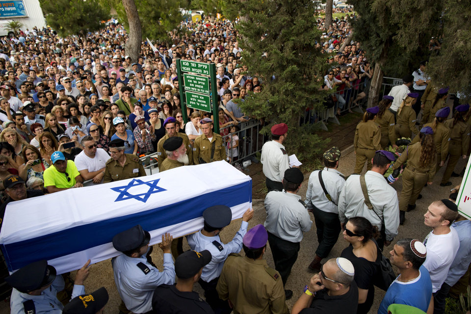 Photo - Israeli soldiers carry the coffin of Israeli Army 2nd. Lt. Hadar Goldin during his funeral at the military cemetery in the central Israeli city of Kfar Saba on Sunday, Aug. 3, 2014. Israel announced that Goldin, a 23-year-old infantry lieutenant feared captured in Gaza, was actually killed in battle. Israel had earlier said it feared he had been captured by Hamas militants Friday near Rafah in an ambush that shattered an internationally brokered cease-fire and was followed by heavy Israeli shelling that left dozens of Palestinians dead. (AP Photo/Oded Balilty)