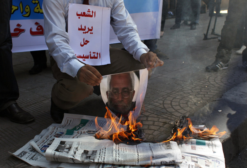 Photo -   An Egyptian protester carries a placard that reads in Arabic,