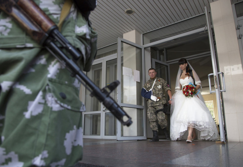 Photo - Platoon commander Arsen Pavlov, also known as Motorola, and Elena Kolenkina exit after their wedding ceremony in the city of Donetsk, eastern Ukraine Friday July 11, 2014. (AP Photo/Dmitry Lovetsky)