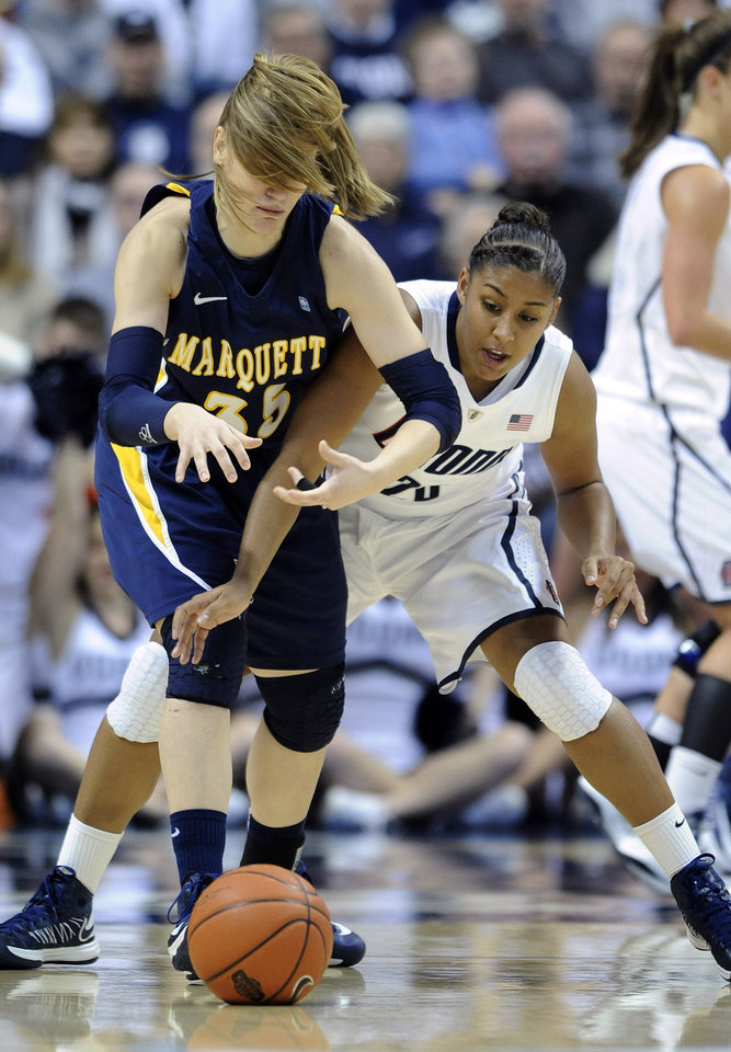 Photo - Marquette's Cristina Bigicaleft, left, fights for a loose ball with Connecticut's Kaleena Mosqueda-Lewis during the first half of an NCAA college basketball game in Storrs, Conn., Tuesday, Feb. 5, 2013. (AP Photo/Fred Beckham)