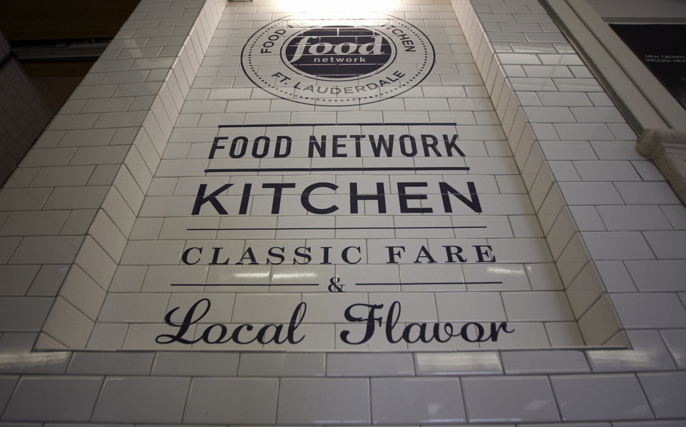 Photo -   In this Wednesday, Nov. 14, 2012 photo, the logo for the Food Network Kitchen is seen at the Fort Lauderdale-Hollywood International Airport in Fort Lauderdale, Fla. Dining-on-the-go is soaring at the airport where travelers can dine at a restaurant inspired by a test kitchen. The Fort Lauderdale-Hollywood International Airport is the first outpost in the nation to offer the Food Network Kitchen, designed to look much like what you would see in the cable network's test kitchen: a butcher block bar counter, subway tiling, stainless steel surfaces and pots and pans hanging in a row behind a cash register. (AP Photo/J Pat Carter)