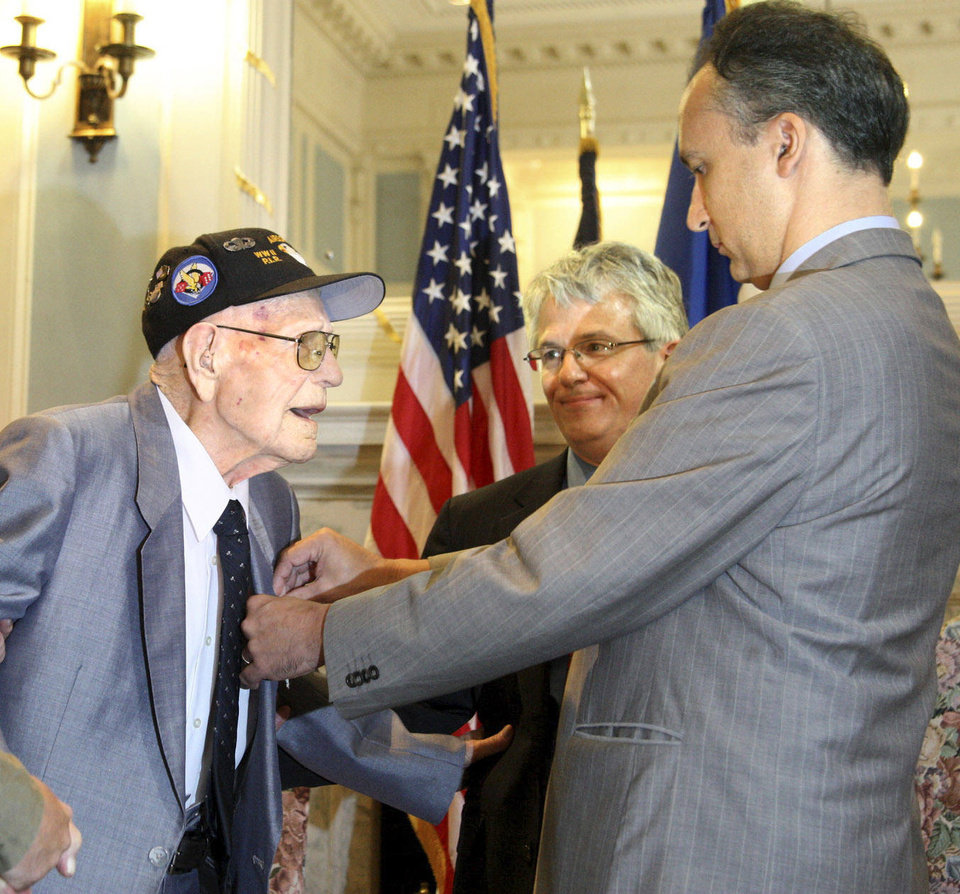 Frederic Bontems, consul general of France, presents Jake McNiece, of Ponca City, with the medal of the Legion of Honor during a ceremony Wednesday at the state Capitol. McNiece, 93, received France\'s most prestigious honor for his World War II combat action during the D-Day invasion of Normandy, France, on June 6, 1944. PHOTO BY LSB PHOTO DIVISION
