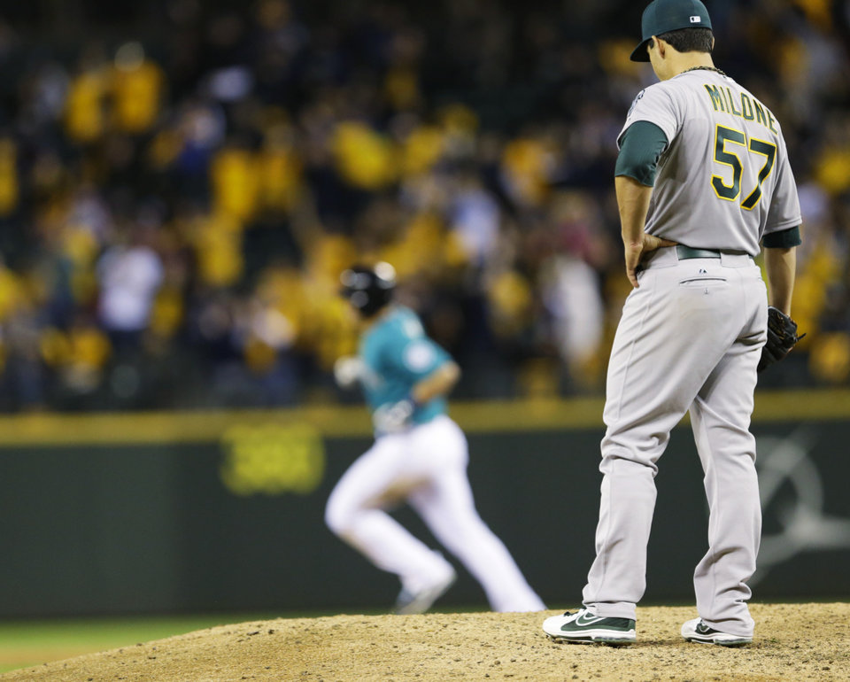 Photo - Oakland Athletics starting pitcher Tommy Milone, right, watches as Seattle Mariners' Mike Zunino rounds the bases on a two-run home run in the sixth inning of a baseball game, Friday, April 11, 2014, in Seattle. (AP Photo/Ted S. Warren)