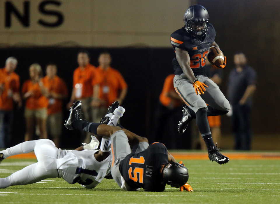 Photo - Oklahoma State's Jeff Carr (20) leaps over player while returning a kick during the college football game between the Oklahoma State Cowboys (OSU) and the Central Arkansas Bears at Boone Pickens Stadium in Stillwater, Okla., Saturday, Sept. 12, 2015. Photo by Sarah Phipps, The Oklahoman
