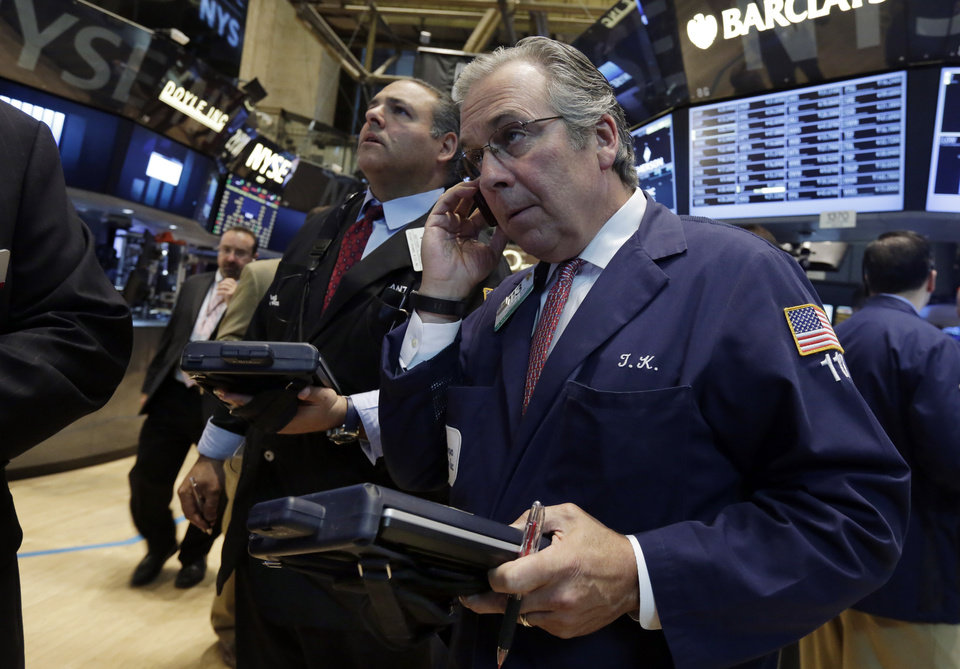 Photo - Traders Anthony Riccio, center, and Thomas Kay, right, work on the floor of the New York Stock Exchange, Tuesday, Aug. 5, 2014. U.S. stock prices are opening lower as traders digest some mixed corporate earnings and a weak indicator on the Chinese economy. (AP Photo/Richard Drew)
