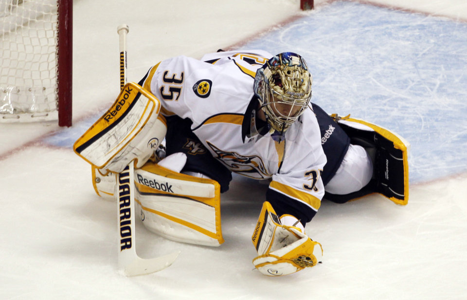 Photo - Nashville Predators goalie Pekka Rinne, of Finland, dives on the ice while making a glove save of a shot from the Colorado Avalanche in the first period of an NHL hockey game in Denver, Saturday, March 30, 2013. (AP Photo/David Zalubowski)
