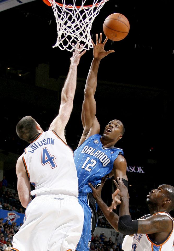 Photo - Orlando's Dwight Howard drives to the basket between Oklahoma City's Nick Collison, left, and Johan Petro during the NBA basketball game between the Oklahoma City Thunder and the Orlando Magic at the Ford Center in Oklahoma City, Wednesday, Nov. 12, 2008. BY BRYAN TERRY, THE OKLAHOMAN   ORG XMIT: KOD