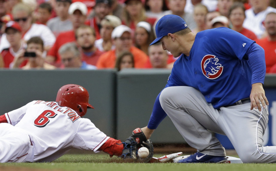Photo - Cincinnati Reds' Billy Hamilton (6) dives safely back to first base as Chicago Cubs first baseman Anthony Rizzo drops a pickoff throw from starting pitcher Edwin Jackson in the first inning of a baseball game, Monday, July 7, 2014, in Cincinnati. (AP Photo/Al Behrman)