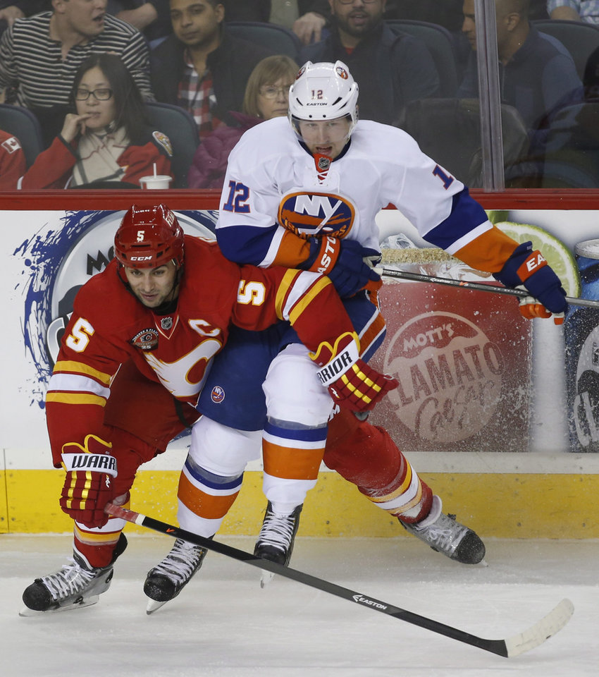 Photo - New York Islanders' Josh Bailey (12) battles Calgary Flames' Mark Giordano during the third period of an NHL hockey game Friday, March 7, 2014, in Calgary, Alberta. (AP Photo/The Canadian Press, Jeff McIntosh)