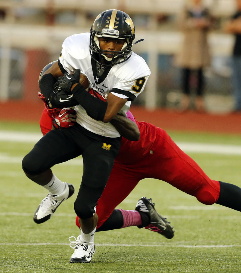 Midwest City's Demeco Wright runs and Del City's Zaviar Sanders tries for a tackle in high school football on Friday, Sept. 20, 2013 in Del City, Okla.  Photo by Steve Sisney, The Oklahoman
